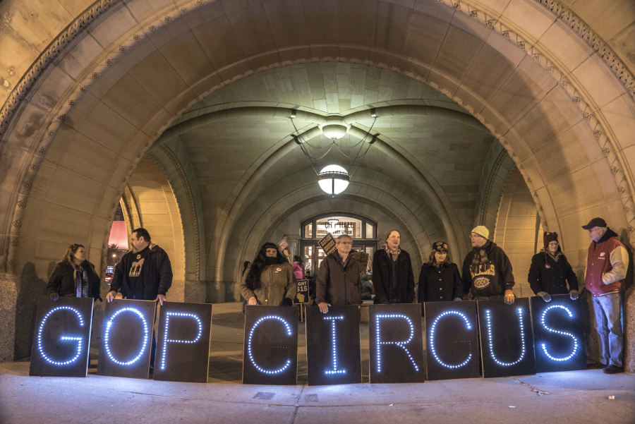 """protesters hold up signs that say """"GOP circus"""""""