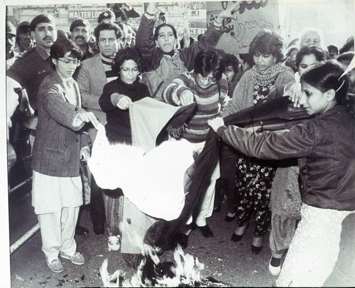a group of women hold fabric over a small bonfire on the ground