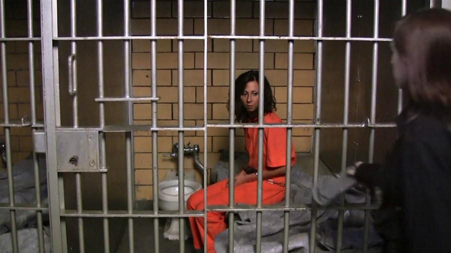 Female prisoner shackled in her small cell