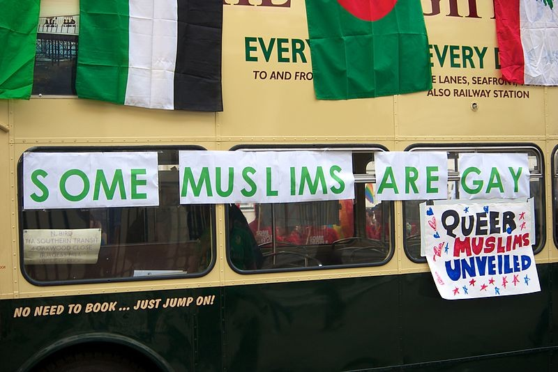 "picture of a bus with protest signs that read ""Queer Muslims United"""