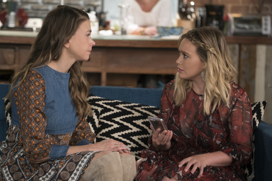 Liza and Kelsey, two white women in print dresses, face each other on a couch