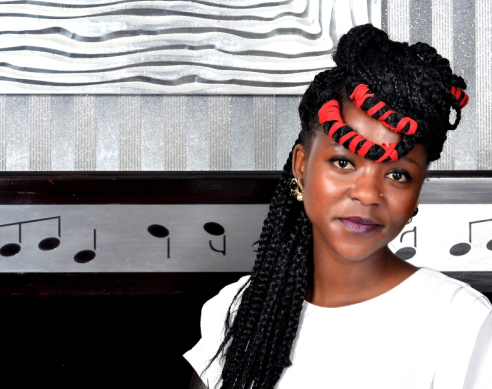 a young, Black woman stands against a wall painted with musical notes