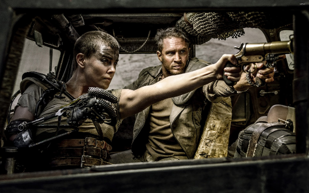 Furiosa with mechanical arm in foreground and normative arm holding gun reaching out the window of truck
