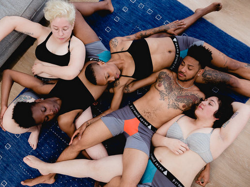 a group of young, multiracial people in bright boxer briefs lie on a bright blue rug