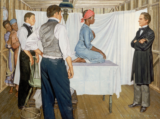Three white men look at a black woman kneeling on an examination table