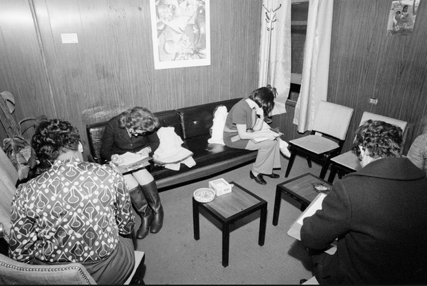 women in a waiting room, hiding their faces from the camera