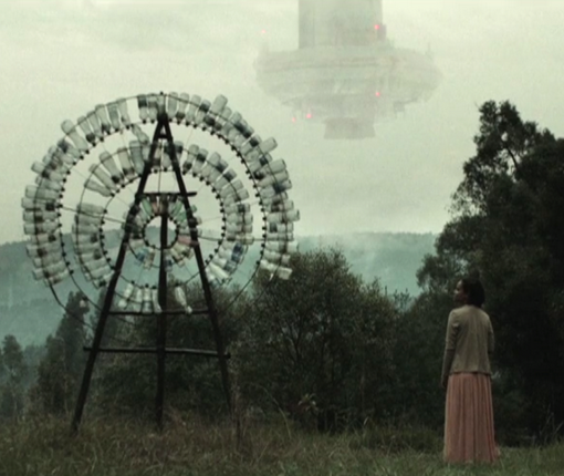 a female figure stands faces away from the screen, a rusted ferris wheel and the shadow of a spacecraft behind itl