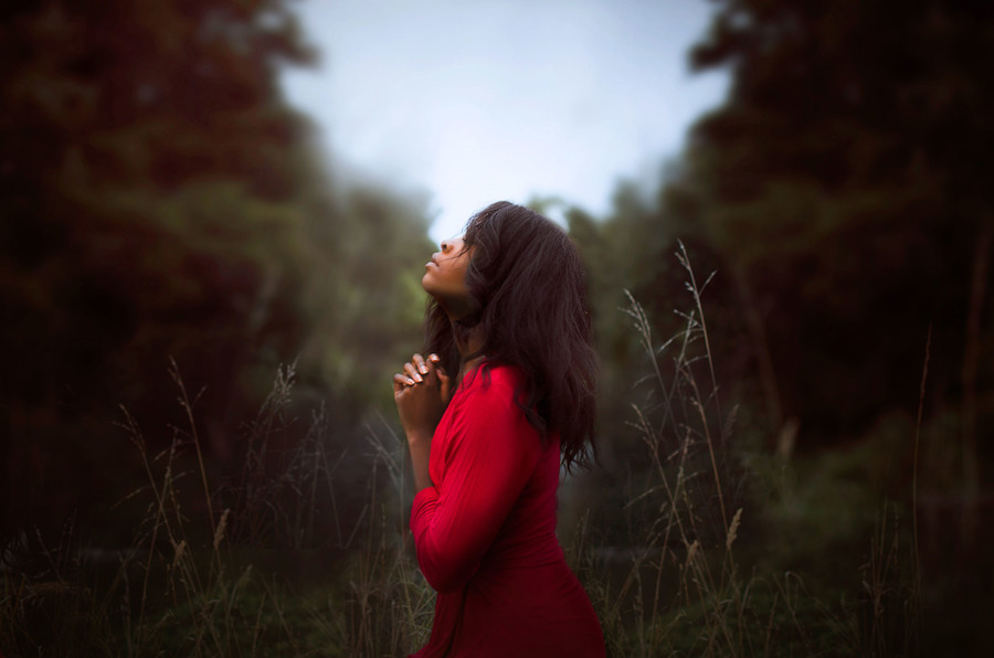 a Black woman in a red dress, with her eyes closed and praying in the middle of a field