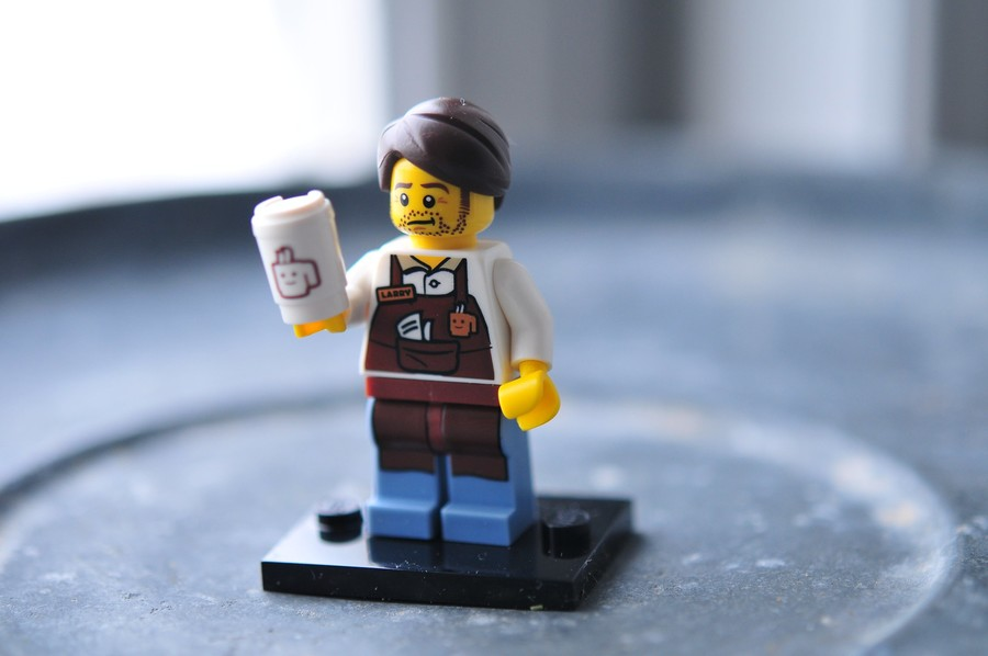 a lego with a beard and short, brown hair holds a coffee cup