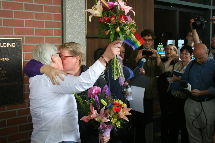 two white women kiss in front of a courthouse in Oregon