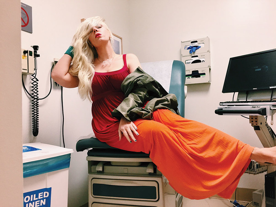 Karolyn Gehrig in an exam room wearing a glamorous red dress