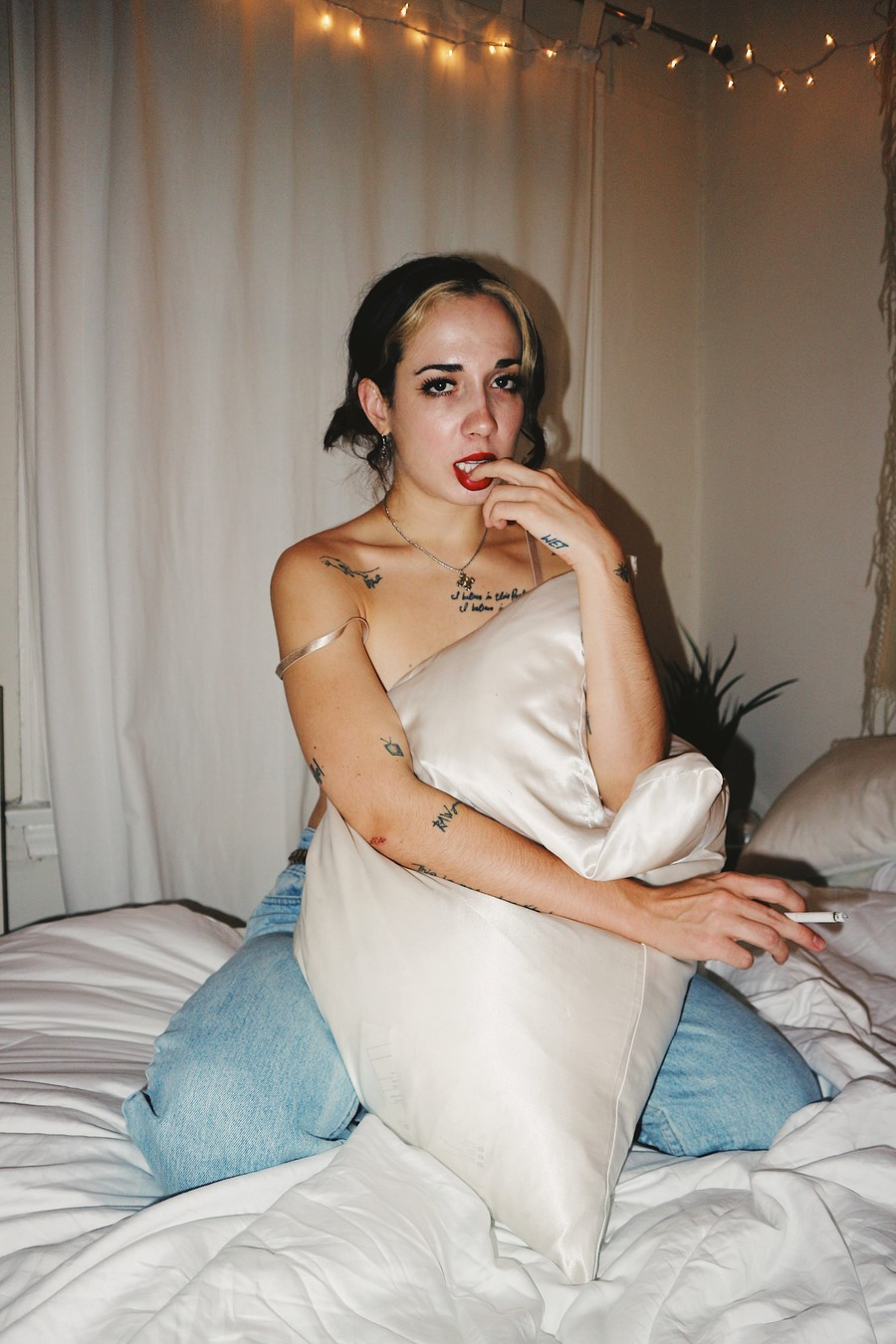 Sizzy Rocket, a white woman, sits on a bed holding a pillow. Her hair is dark and she's pouting, and she has many tattoos.