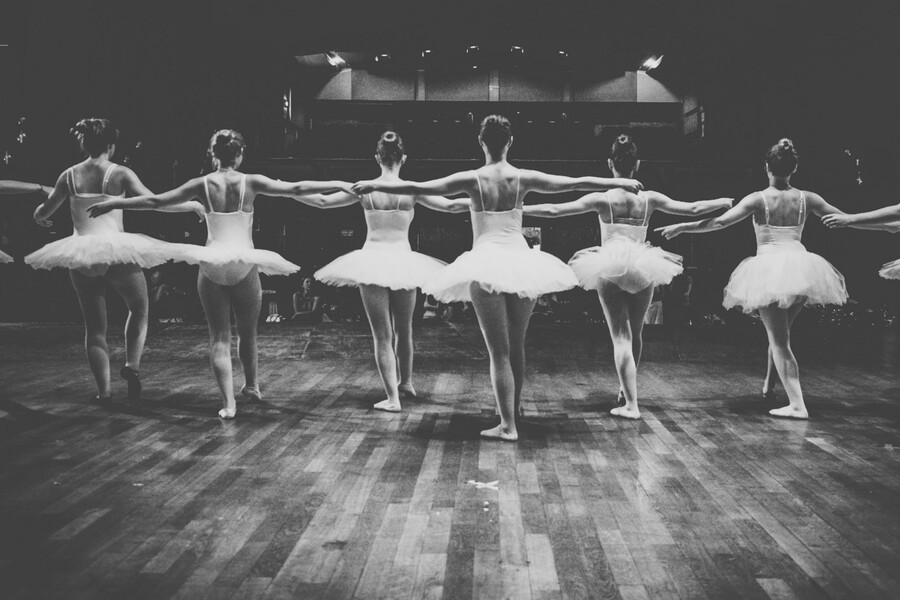 a black and white photo showcases a row of thin, white ballerinas in tutus on a stage, with their backs facing the camera