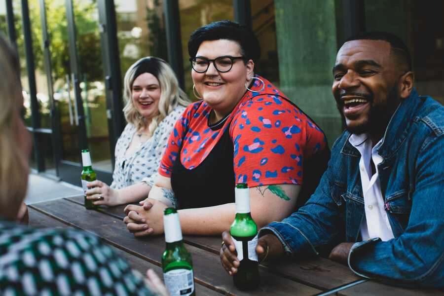 a thin white person, a fat white person, and a brown-skinned Black person sit together on a patio, drinking beers in green bottles and laughing