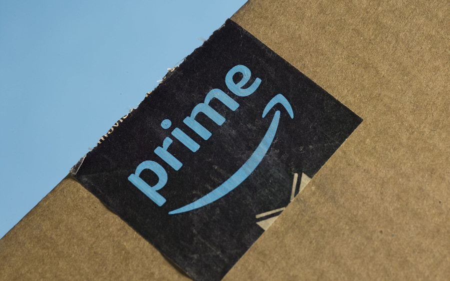 Closeup of a cardboard box with an Amazon Prime sticker against a bright blue background