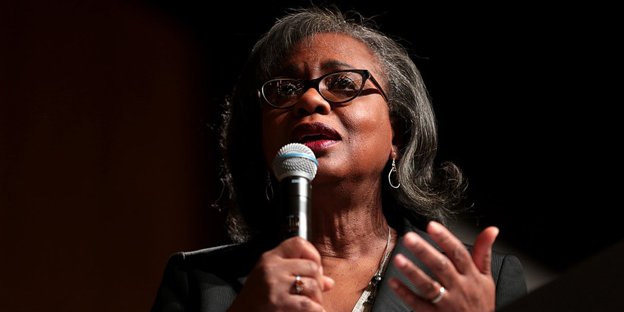 Anita Hill holding a microphone and gesturing with her other hand while giving a lecture