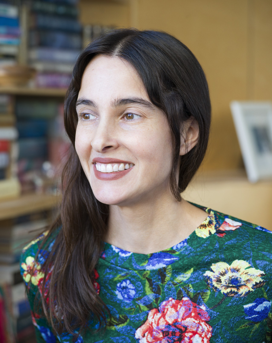 Donna Freitas, a white woman professor with long, black hair, smiles at the camera