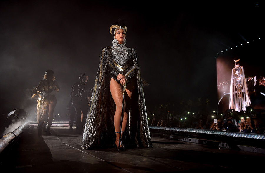 a lightskinned Black woman wears a regal outfit on a stage