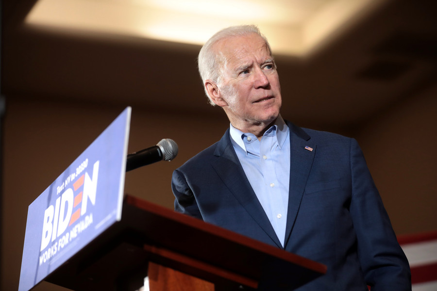 Joe Biden, an elderly white man with short, gray hair, stands behind a podium while wearing a blue blazer