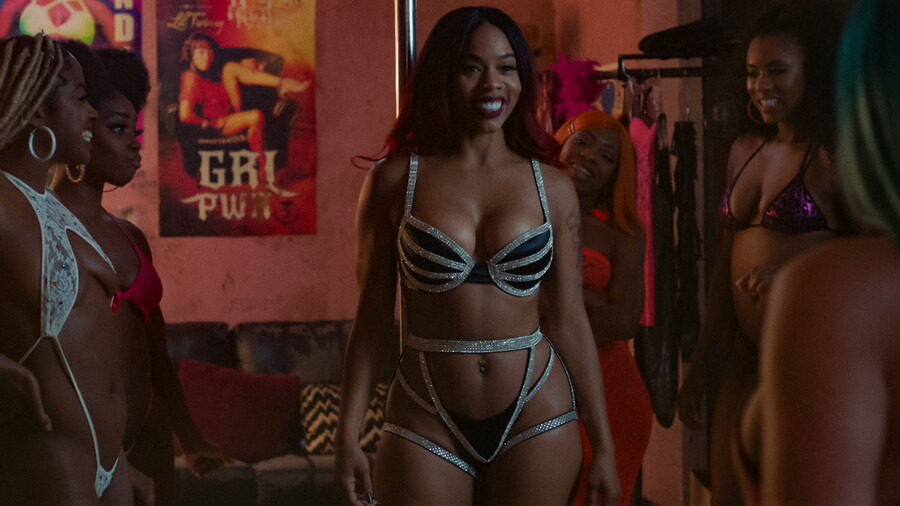 Brandee Evans plays Mercedes, a Black woman wearing a long, black wig, and standing among other Black women in a glittery, two-piece suit