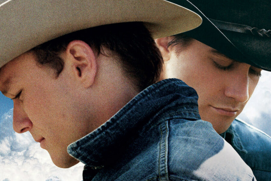 Heath Ledger (left) wearing a jean jacket and white cowboy hat looking downward to the left of the frame. Jake Gyllenhaal stands behind him (right), wearing a black cowboy hat and jean jacket and looking downward to the right of the frame
