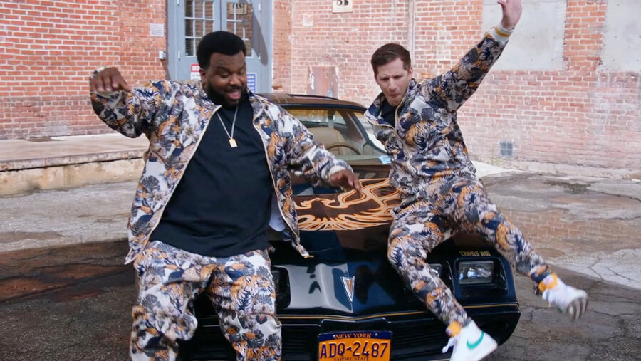 Doug Judy, left, and Andy Samberg wear matching tiger track suits and sit on the hood of a car that has a bird decal on the hood