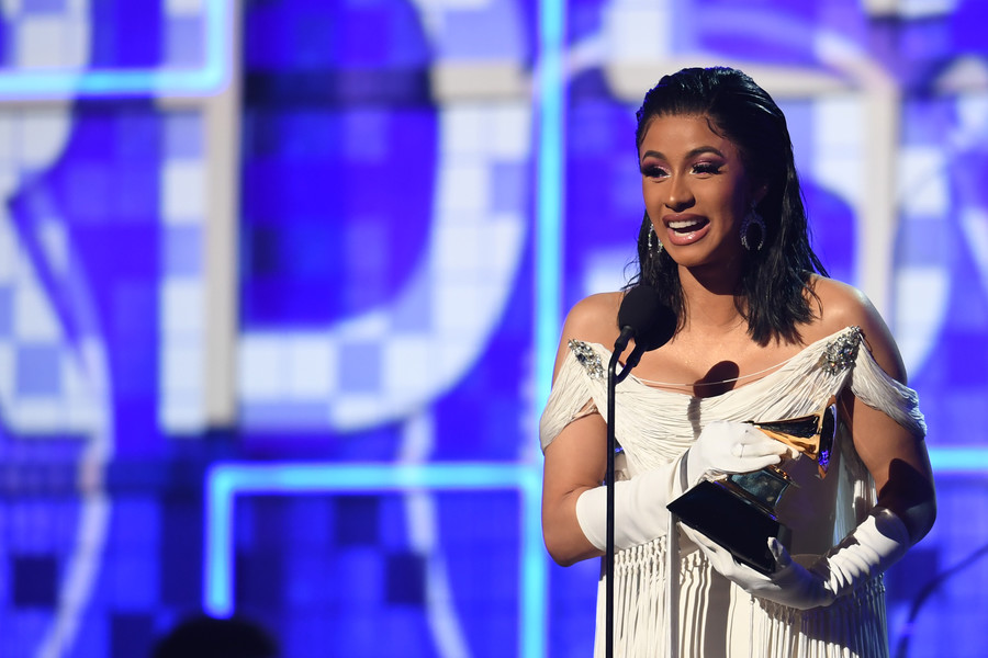 a Latinx woman with wavy, Black hair wins a Grammy award