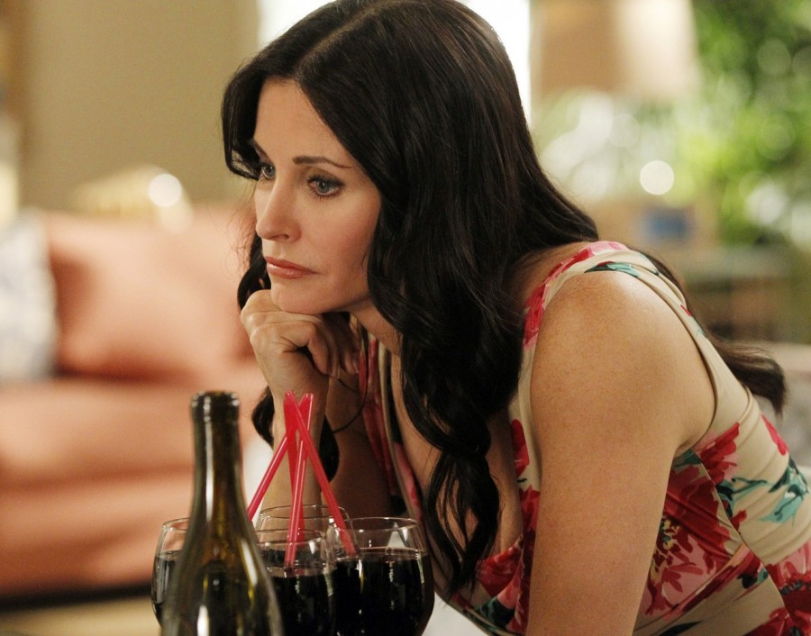 Courteney Cox as Jules Cobb on Cougar Town sitting in front of five glasses of dark wine