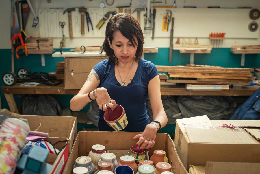 Lujan Agusti, a Latinx woman with differing abilities, classifies materials at a ceramics studio