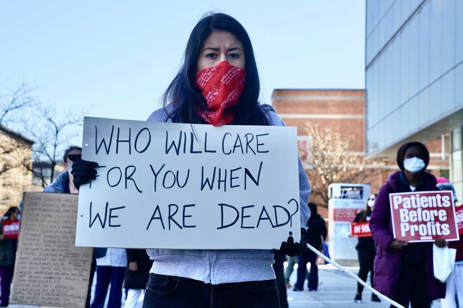 A nurse with short dark hair stands outside holding a sign that reads,
