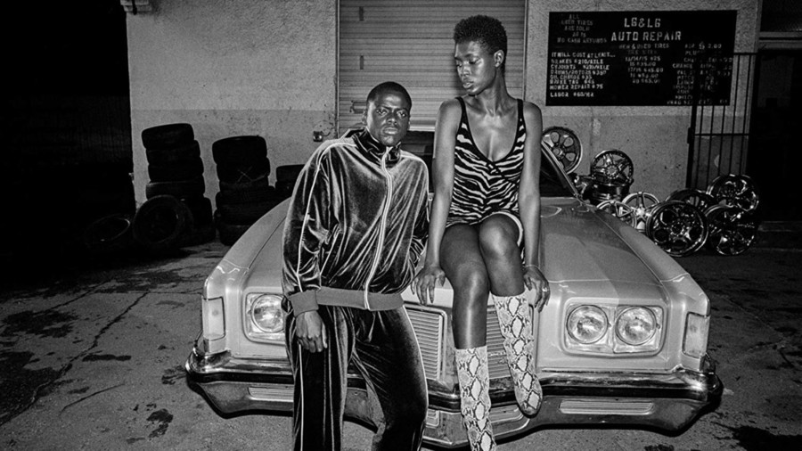 a Black man and a Black woman pose in front an old-school Chevy in Queen & Slim