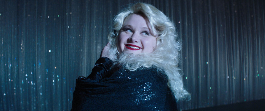 a plus-size white teen with long, blonde, curly hair smiles at a flashing camera