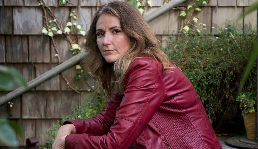 Dr. Jen Gunter, a white doctor with long, brown hair and wearing a red leather jacket. sits on concrete stairs