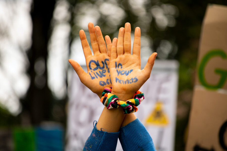 """A pair of hands raised in protest with the words """"Our lives are in your hands"""""""