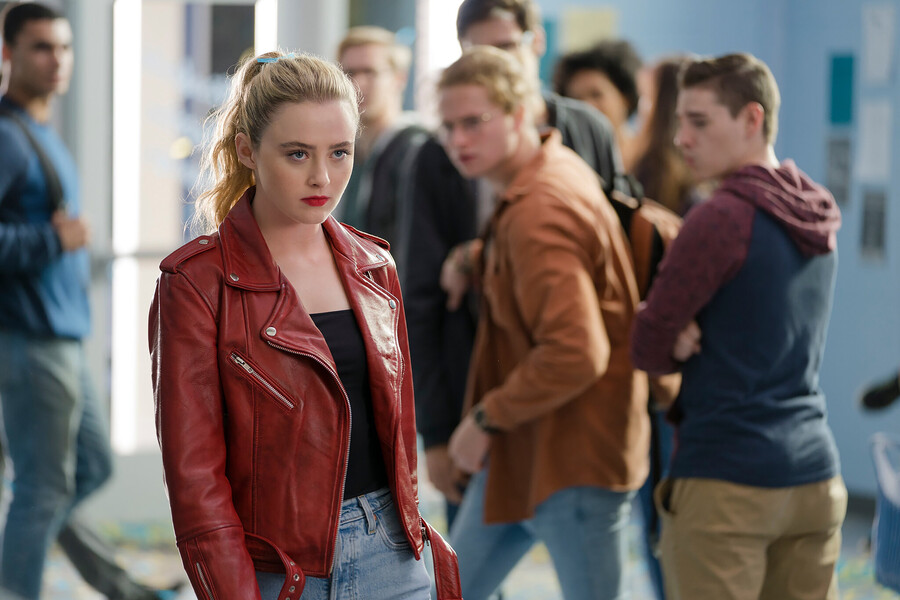 Kathryn Newton wearing a red leather jacket, jeans, and red lipstick staring angrily in the middle of a school hallway as other students gawk at her