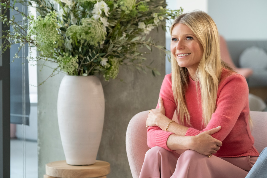 Gwyneth Paltrow, a white woman, wears a yellow dress. She sits on a fancy couch and smiles.