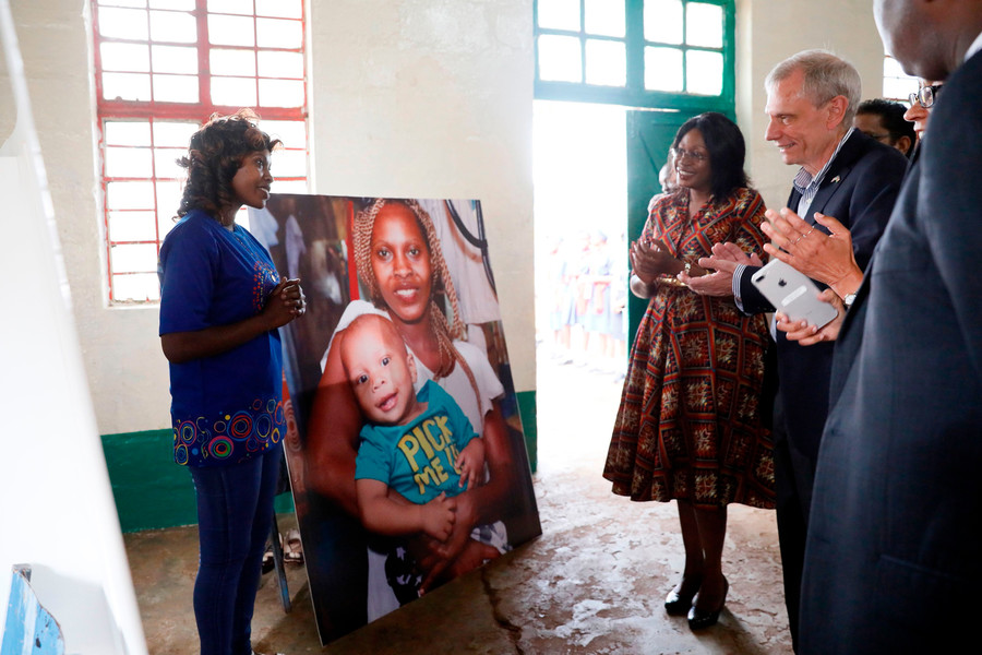 a group of people stand around a poster board image of a Black woman holding a baby