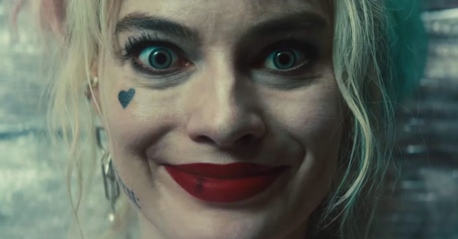 Margot Robbie as Harley Quinn, a white woman with bleach blond hair, smiles at the camera. She has bright blue eyes and a heart tattooed on her cheek, in Birds of Prey