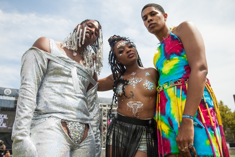 brownskinned Black person with a gray outfit, brown woman topless with an elephant over her stomach and pasties on her breasts, and a lightskinned Black person in a rainbow-colored jumpsuit