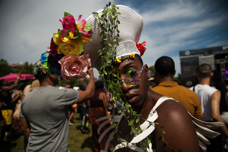 brownskinned Black person wearing sunglasses and a white hat covered in leaves and flowers