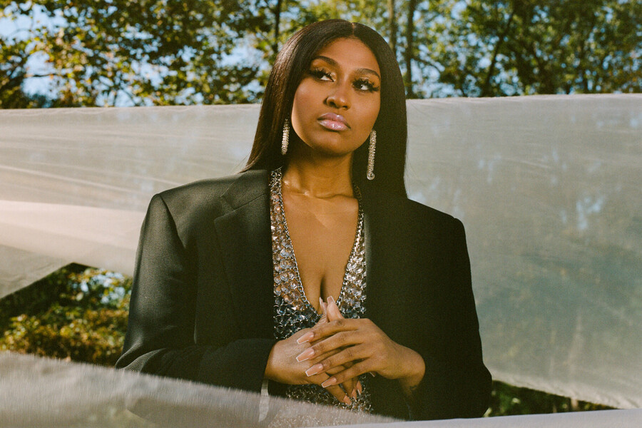 Jazmine Sullivan, a dark-skinned Black woman with silky, long, black hair, poses against a gray background while wearing a bedazzled shirt and black blazer