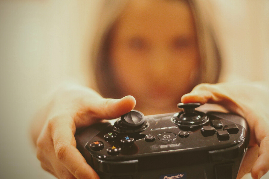 a blond-haired woman whose face is blurred out holds a black video-game controller in her hands