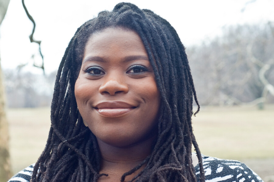 Kaitlyn Greenidge, a dark-skinned Black woman with long black locs, stands outside and smiles slightly