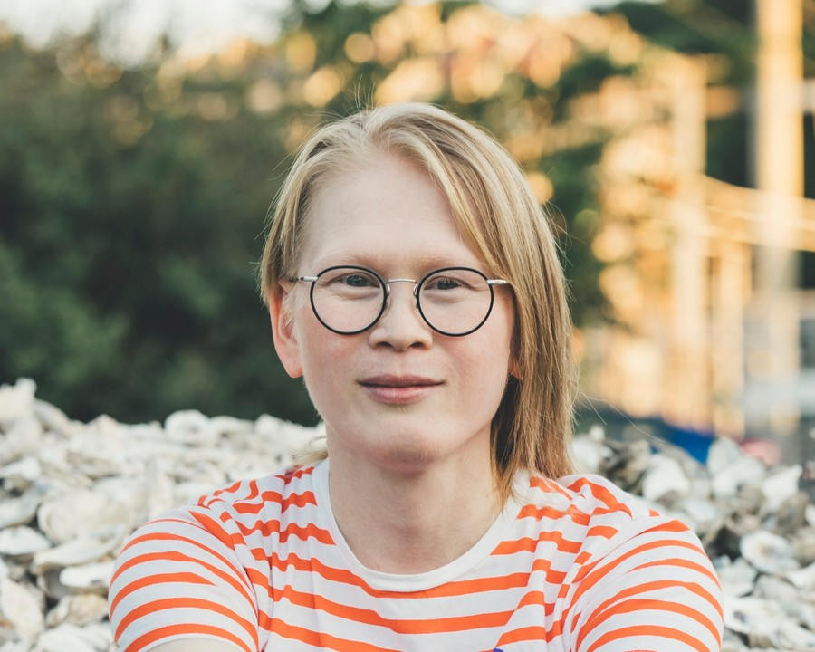 Meredith Talusan, an Albino Filipino woman, has blond hair and wears a striped orange t-shirt as she smiles gently.