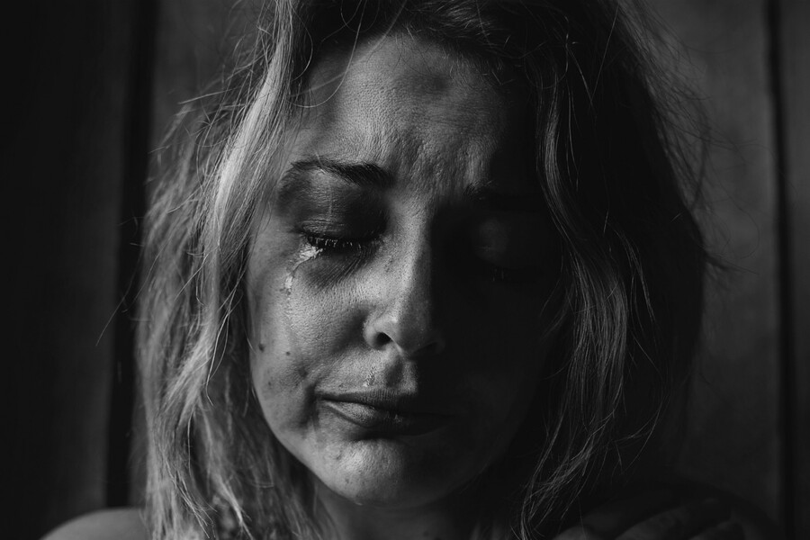 a black and white photo of a white woman with short hair closing her eyes as tears streak down her face