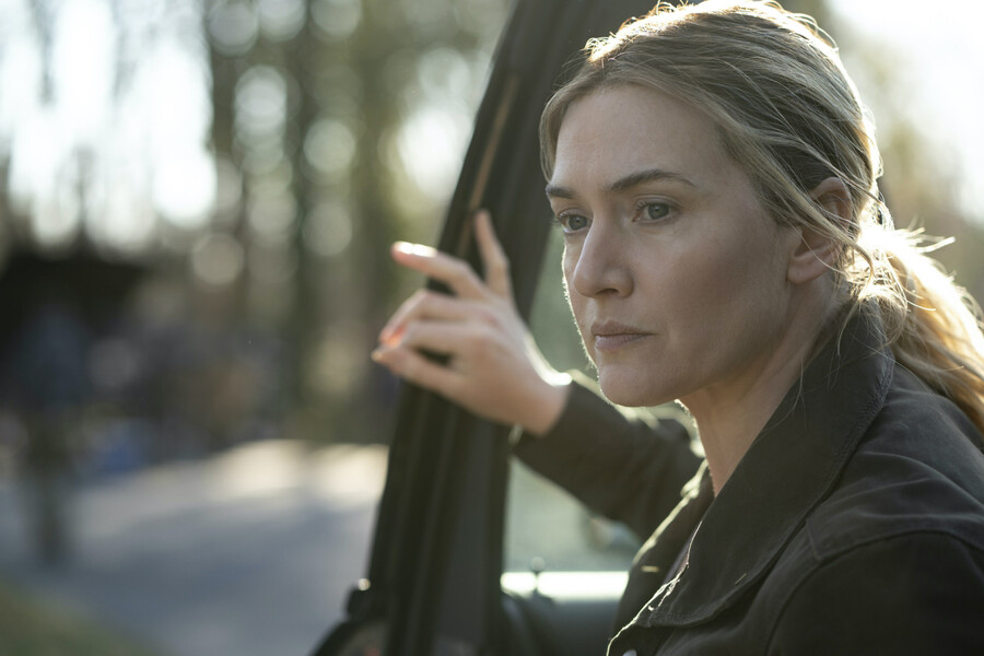 Kate Winslet plays Mare Sheehan, a white woman with blue eyes and her blond hair in a ponytail, in Mare of Easttown