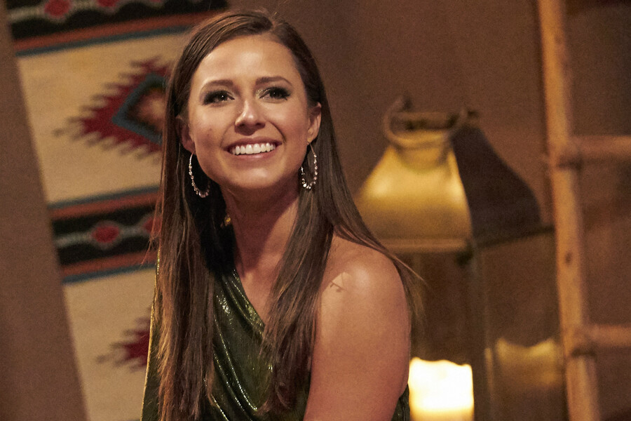 Katie Thurston, the new Bachelorette, is a thin, white woman with long, brown hair who is sitting on a chaise and smiling in a sparkly green dress