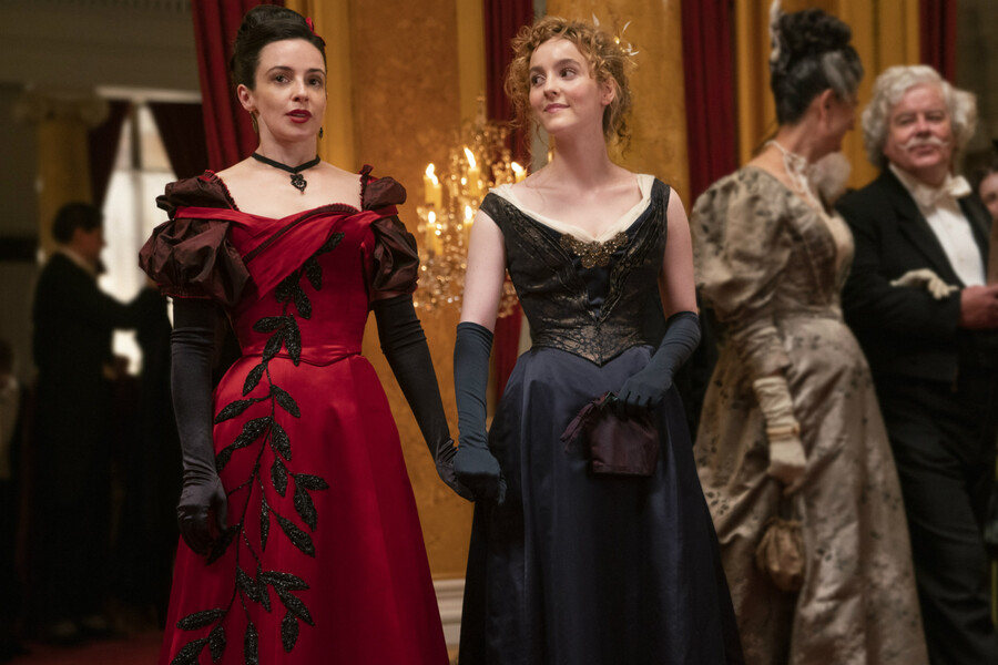 Laura Donnelly and Ann Skelly play Amalia and Penance, two white women wearing a red and black gown, and holding hands in The Nevers