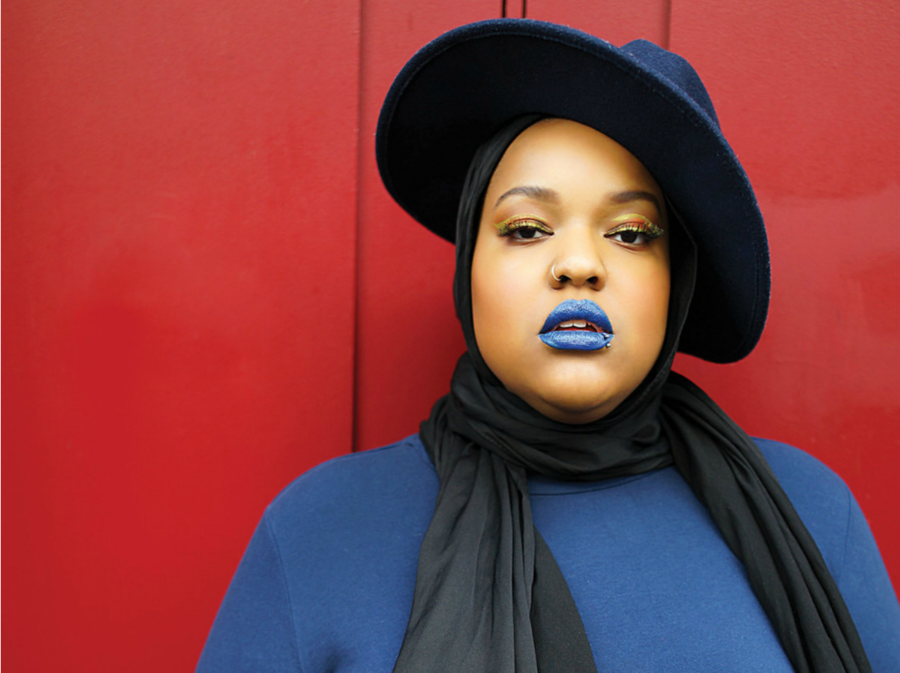 Leah Vernon, a fat Muslim woman, wearing a navy blue hat, black head scarf, yellow mascara, blue lipstick, against a red wall