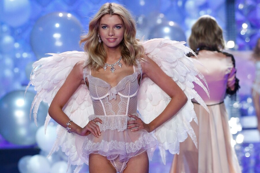 Stella Maxwell, a Victoria's Secret Model who is white with blond hair, stands with her hands on her hips in white, lace lingerie and white wings on her back making her look like an angel